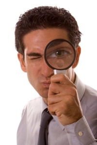 Man holding a magnifying glass over his eye
